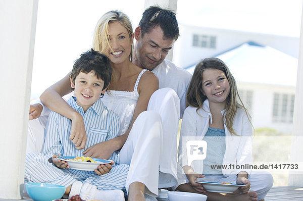 Paar und zwei Kinder beim Essen  auf der Holzterrasse sitzend