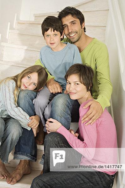 Paar und zwei Kinder lächeln für die Kamera  sitzen auf der Treppe