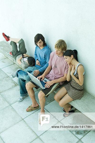 Gruppe junger Freunde auf der Bank sitzend  mit Laptop