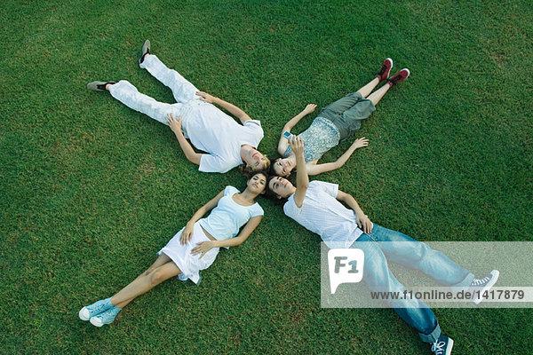 Gruppe junger Freunde  die auf Gras liegen  Köpfe zusammen