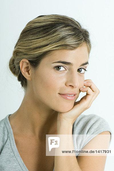 Frau lächelt vor der Kamera  Hand unter dem Kinn  Kopf und Schultern  Porträt