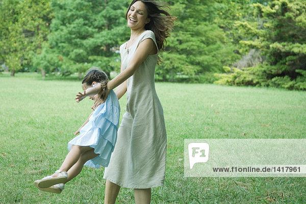 Frau schwingende Tochter auf Gras