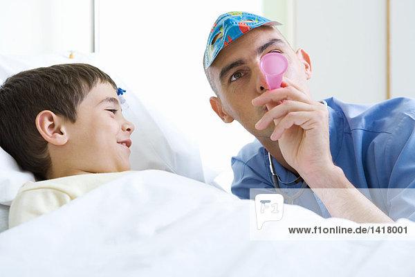 Praktikant neben dem Jungen im Krankenhausbett  mit Maske und Blashorn