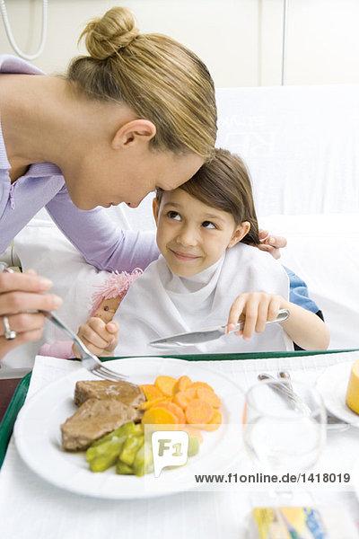 Mädchen sitzt im Krankenhausbett und lächelt die Mutter beim Essen an.