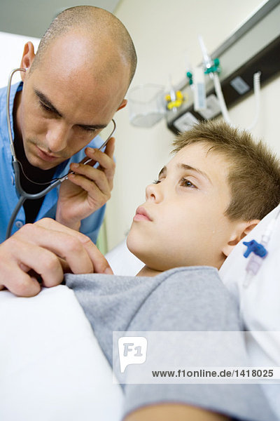 Boy lying in hospital bed  intern listening to boy's chest with stethoscope