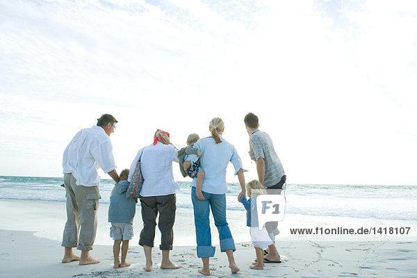 Drei Generationen Familie am Strand stehend