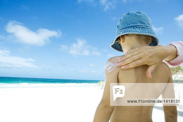 Weibliche Hand  die Sonnencreme auf den nackten Rücken des Jungen am Strand aufträgt.