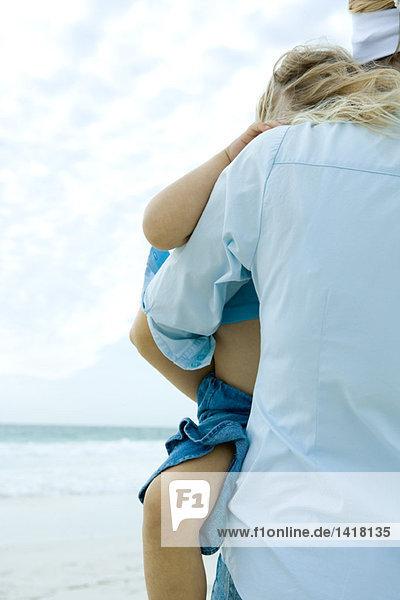 Kleines Mädchen wird von Mutter am Strand getragen  Teilansicht