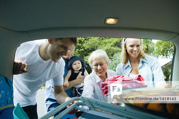 Familie beim Entladen von Strandmaterial aus dem Kofferraum des Autos