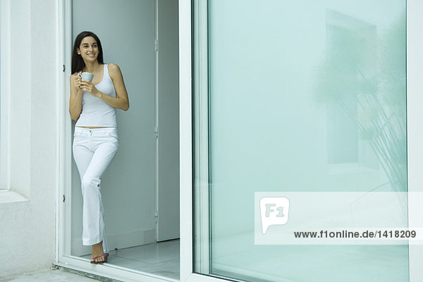 Woman standing in doorway with cup  smiling  full length