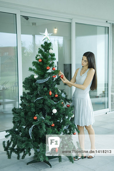 Woman putting decorations on Christmas tree  full length