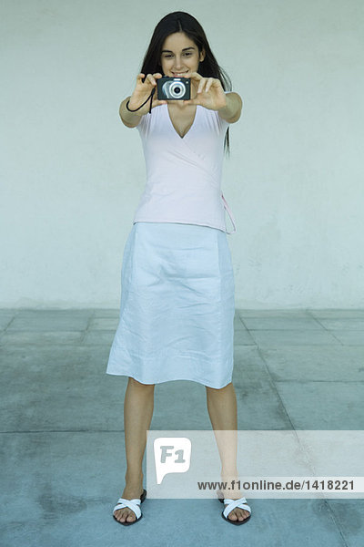 Woman standing taking photo with digital camera  full length