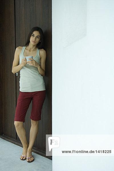 Frau steht in der Nähe der Tür  Halteschale  volle Länge