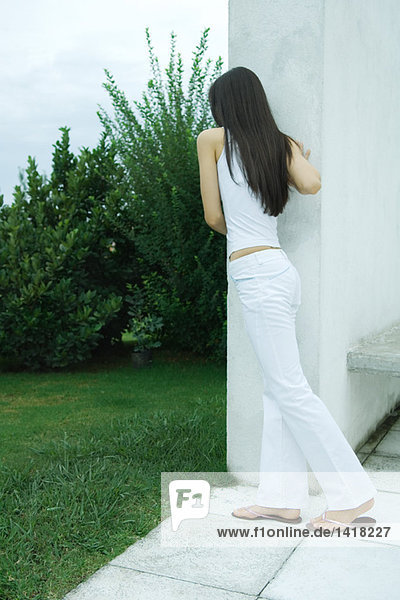 Woman leaning against corner of wall  rear view  full length