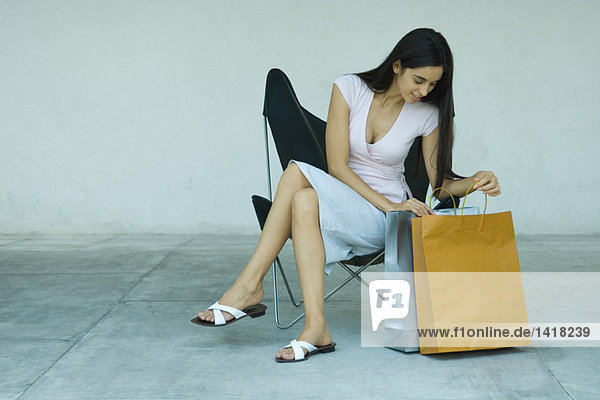 Woman sitting  looking in shopping bags  full length