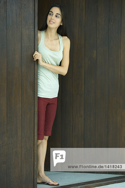 Woman looking out of doorway  full length