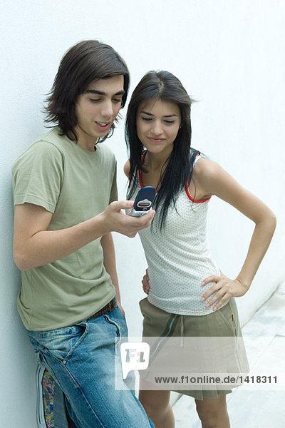 Junges Paar lehnt sich an die Wand  schaut auf das Handy