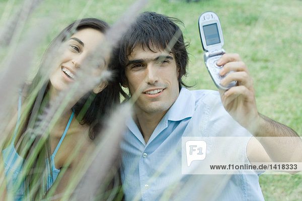 Young couple taking photos of selves with cell phone