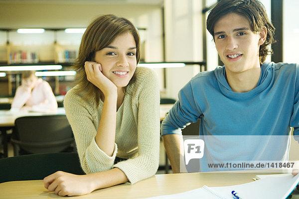 Studenten sitzen am Tisch in der Bibliothek und lächeln vor der Kamera.