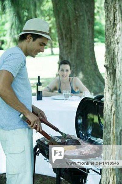 Mann beim Grillen von Fleisch auf dem Grill