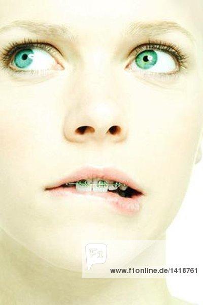Teenagermädchen mit Klammern beißende Lippe  extreme Nahaufnahme  Mund
