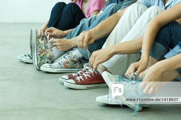 Vier Teenager-Freunde mit Schnürsenkeln  die alle Leinenschuhe tragen. Vier Teenager-Freunde mit Schnürsenkeln, die alle Leinenschuhe tragen.