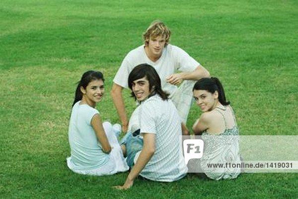 Vier junge Freunde sitzen auf Gras und schauen in die Kamera.