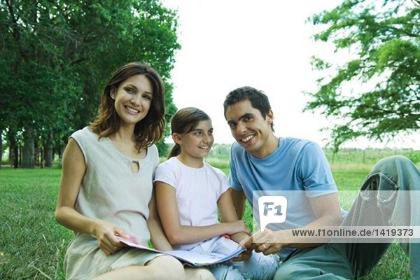 Familie im Freien sitzen  gemeinsam lesen