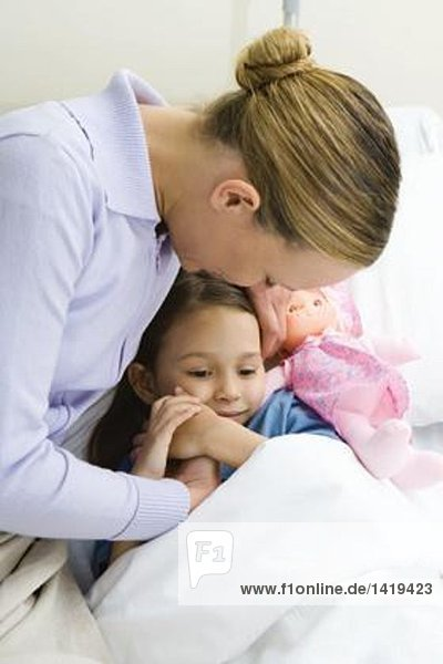 Frau hält Hände mit Tochter im Krankenhausbett