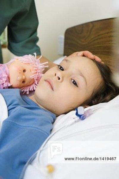 Mädchen im Krankenhausbett liegend