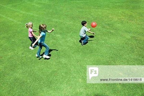 Kinder beim Ballspielen auf Rasen