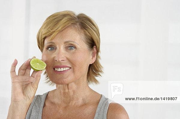 Alte Frau hält eine Scheibe Limette vors Gesicht  fully_released