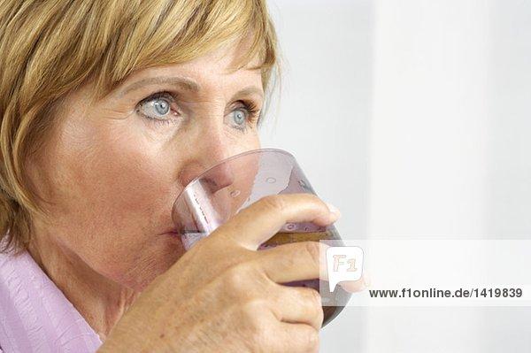 Alte Frau trinkt ein Glas Wasser mit Zitrone  fully_released