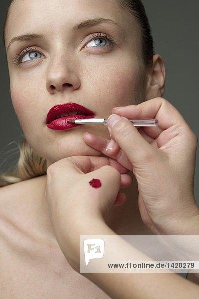 Junge Frau bekommt Lippen geschminkt  fully_released