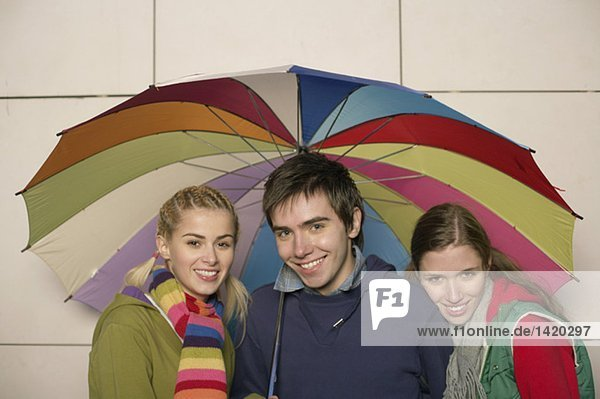 Gruppe junger Leute unter einem Regenschirm  fully_released