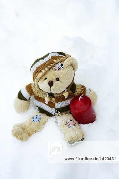 Teddybär und eine Kerze im Schnee  fully_released