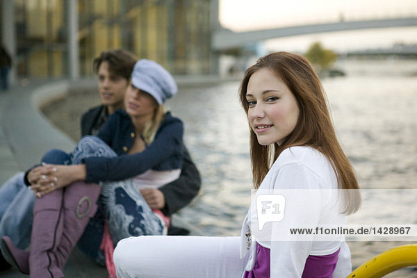Young woman sitting at river  couple in background