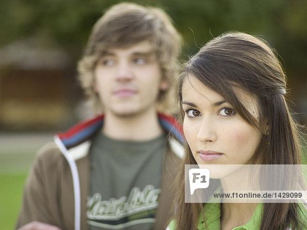 Junge Frau  Portrait  junger Mann im Hintergrund