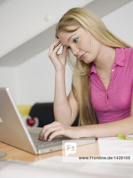 Junge Frau auf dem Schreibtisch sitzend  mit Laptop