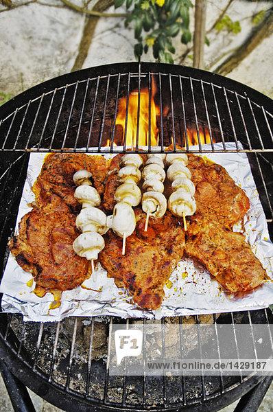 Fleisch und weiße Champignons auf dem Grill