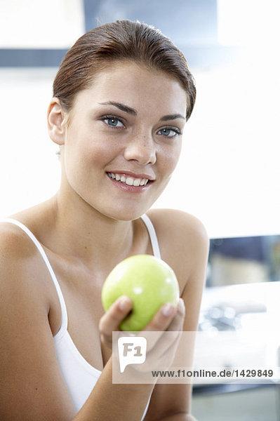 Junge Frau mit Apfel in der Hand