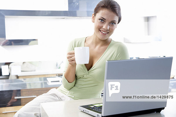 Woman sitting in kitchen  with laptop  holding cup