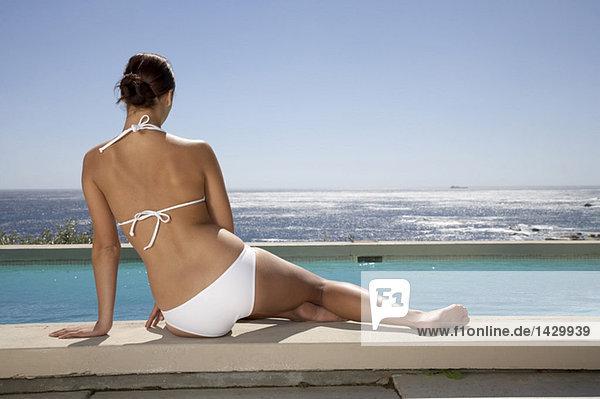 Frau am Schwimmbad sitzend  Rückansicht