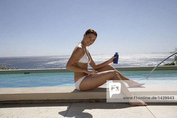 Woman applying suncreme  sitting at swimmingpool