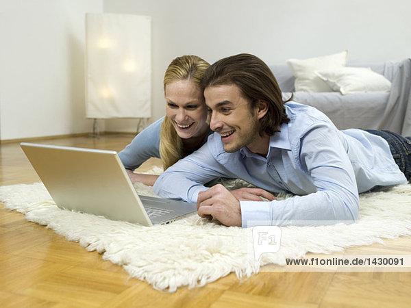 Paar auf dem Boden liegend  mit Laptop