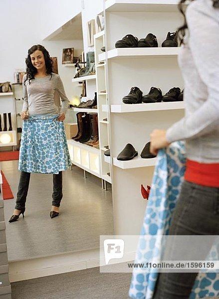 Eine Frau vor einem Spiegel in einem Geschäft.