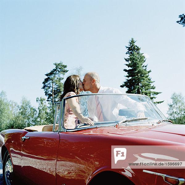 Ein paar küssen in einem Auto.