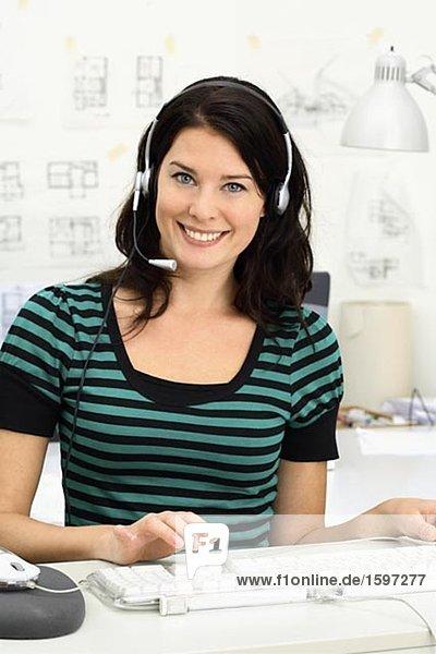 Eine Frau mit Headset in einem Büro.