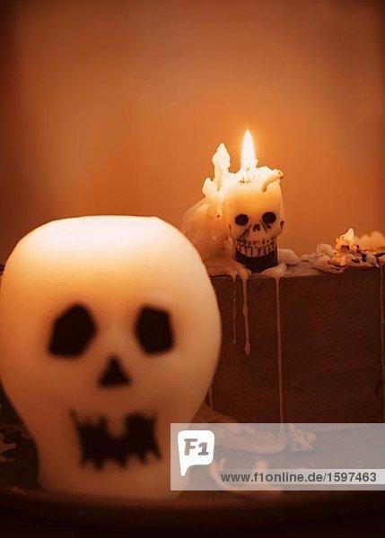 Schädel und brennenden Kerzen während Halloween.