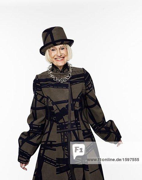 Eine lächelnd ältere skandinavischen Frau in einem schönen Hut und Mantel.